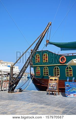 RETHYMNO, CRETE - SEPTEMBER 15, 2016 - View of a Galleon ship and crane in the inner harbour with waterfront restaurants to the rear Rethymno Crete Greece Europe, September 15, 2016.