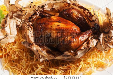 Baked chicken served in paper with fried potato. Delicious american traditional dining. Junk food, fat concept