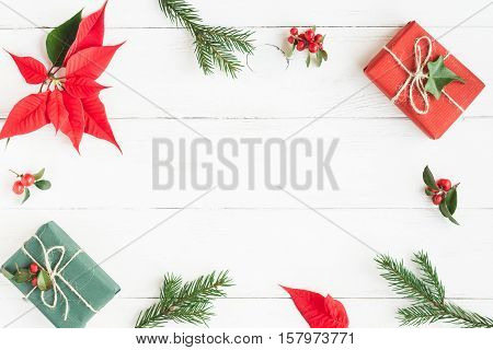 Christmas frame. Gifts fir branches christmas poinsettia. Flat lay top view
