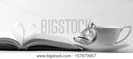 Pocket watch cup and open book on white