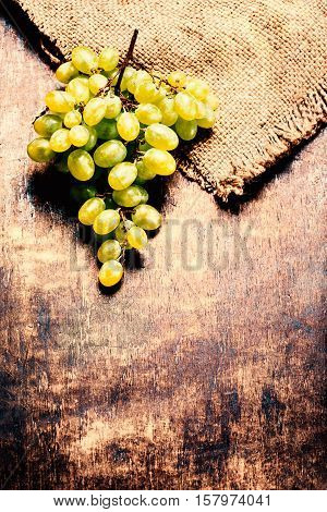 White Wine grape bunch over wooden background. Green grapes macro vintage image