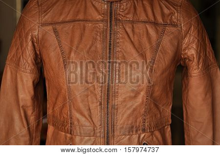 Close up of brown leather jacket with details. Leather texture with linear stitches are clearly visible. The image is part of a leather jacket without any human face or body part.