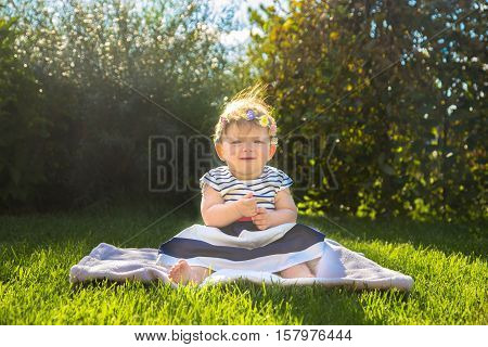 Beautiful baby girl on the green grass. Happy childhood