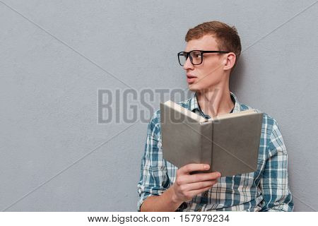 Young student in glasses with book. looking away. isolated gray background