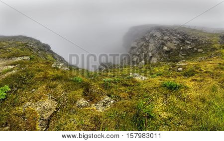 North Cape (Nordkapp) on the northern coast of the island of Mageroya in Finnmark Northern Norway on heavy foggy day .