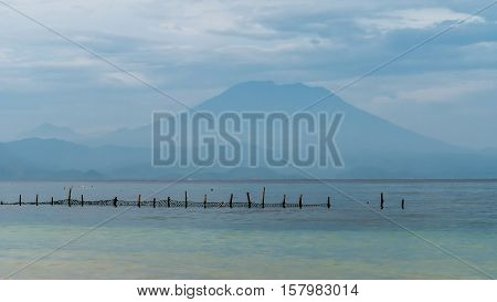 Beautifull evening view to St. Agung Vulcano on Bali from Nusa Penida Island, Net in front some Clouds in Background.