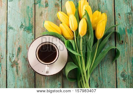 Coffee Mug With Yellow Tulip Flowers On Green Rustic Table From Above, Breakfast On Mothers Day Or W