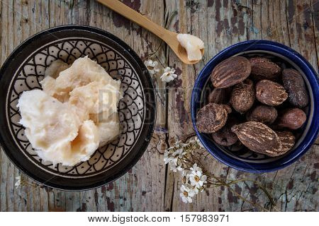 Shea butter and nuts on wood flat lay