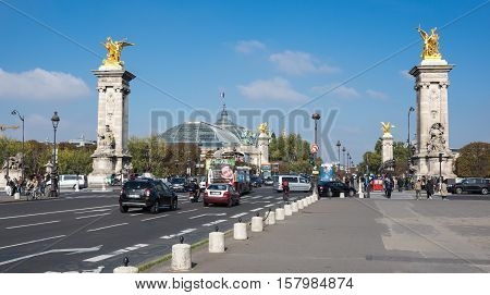 PARIS FRANCE - OCTOBER 11 2015: The Pont Alexandre III is a deck arch bridge that spans the Seine in Paris France. The bridge is widely regarded as the most ornate extravagant bridge in the city