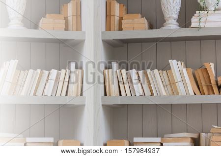 Bookshelf is white book with wooden white shelf background effect light.