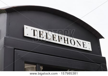 Vintage big black pay phone on white sky.