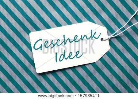 German Text Geschenk Idee Means Gift Idea. One Label On A Turquoise Striped Wrapping Paper. Textured Background. Tag With Ribbon.