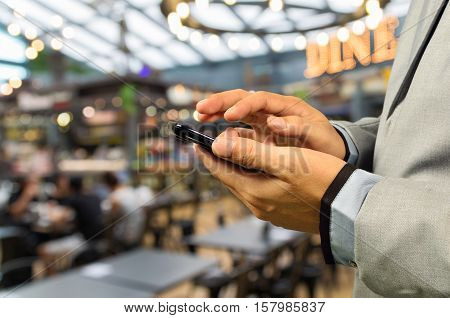 Man Using Smartphone Or Cellphone In Café Or Restaurant