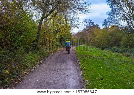 Man runs with bicycle through forest. Man biking through forest with a basket carrying children to school.