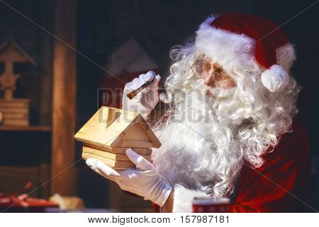 Merry Christmas and Happy Holidays! Santa Claus is preparing gifts for children for Xmas at his desk at home. Christmas legends and traditions.