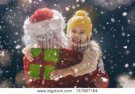 Merry Christmas and happy holidays! Cute little child girl hugging Santa Claus and holding a gift. Christmas legend concept.
