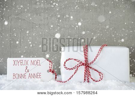 One Christmas Present On Snow. Cement Wall As Background With Snowflakes. Modern And Urban Style. Label With French Text Joyeux Noel Et Bonne Annee Means Merry Christmas And Happy New Year