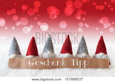 Label With German Text Geschenk Tipp Means Gift Tip. Christmas Greeting Card With Gnomes. Sparkling Bokeh And Red Background With Snow.