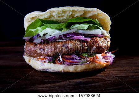 Homemade hamburger with fresh vegetables on wood background