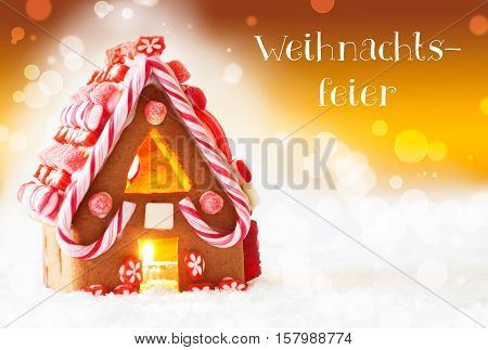German Text Weihnachtsfeier Means Christmas Party. Gingerbread House In Snowy Scenery As Christmas Decoration. Candlelight For Romantic Atmosphere. Golden Background With Bokeh Effect.