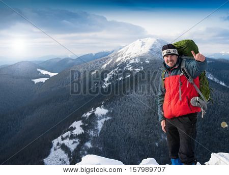 Hiker on the mountain top. Sport and active life concept. Man on peak of mountain. Emotional scene. Hiker at the top of a rock with backpack enjoy sunny day.Thumbs-up Hiker smiling.