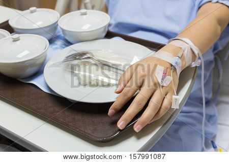 Asian Pregnant Woman patient is on drip receiving a saline solution with cooked rice and other food in white bowl selective focus.