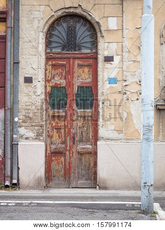 Picture of the front door with wrought iron grill. Some of the red paint has scaled off. An old building with cracky beige - coloured paint and rusty gutter. Background of the old building