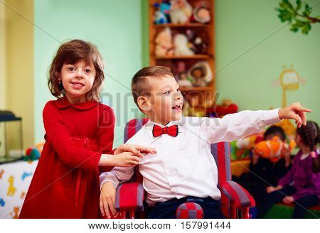 Cute Little Gentleman In Wheelchair And Lady On Holidays In Kindergarten For Kids With Special Needs