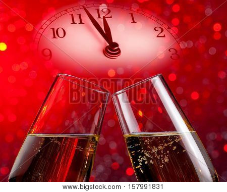 champagne flutes with golden bubbles make cheers on red light bokeh background with vintage alarm clock is showing midday or midnight happy new year concept