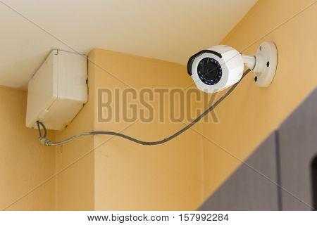 The CCTV security camera operating on orange cement wall inside room.