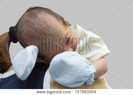 Asian cute new born baby on shoulder mom after crying.