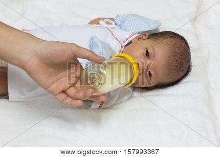 Asian cute new born baby eatting mlik mother in bottle mum feeding on white towel background.