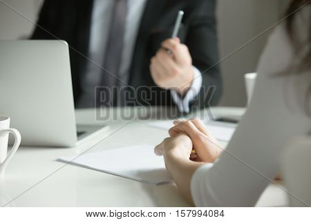 Close up of female hands, nervously clutched. The woman feels stressed, she is scolded by her boss, or is on job interview. Business concept photo