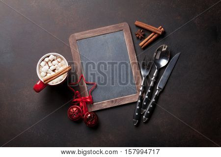 Chalkboard for your christmas menu, hot chocolate and silverware. Top view with copy space