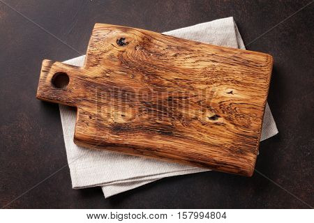 Cutting board over towel on stone kitchen table. Top view