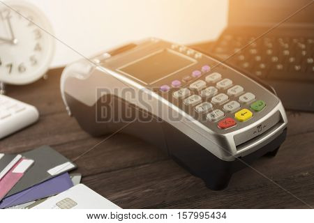 Credit Card Terminal or EDC on cashier wooden table in the store with calculator clockcredit cards and laptop on wooden background with copy space.