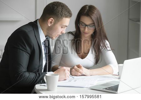 Businessman and businesswoman at office desk, working together, man instructing and coaching woman to give her an opportunity to grow and achieve optimal performance. Business concept photo
