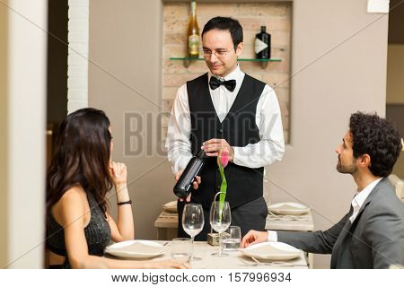 Waiter suggesting a bottle of red wine to a couple at the restaurant