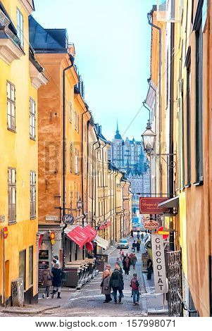 STOCKHOLM, SWEDEN - APRIL 14, 2010: People on Tyska Brinken (The German Slope) Street with boutiques and cafes in Gamla Stan (Old Town). The street is named after The German Church and parish