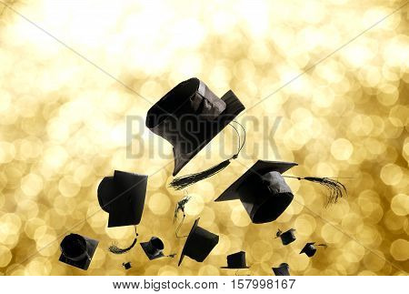 Graduation Ceremony, Graduation Caps, Hat Thrown In The Air With Gold Light Abstract Background.