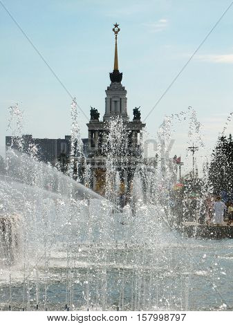main pavilion VDNKH in Moscow through fountain streams.