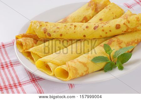 plate of empty rolled pancakes on checkered dishtowel - close up