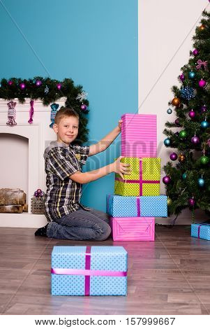 Smiling boyl sitting on the floor next to the presents and a tree