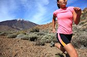 Running. Woman Cross country trail runner running on the mountain / volcano Teide on Tenerife. Beautiful mixed chinese asian / caucasian female model. poster