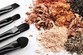 four makeup brushes and crumbled eyeshadow of different colors on a white background horizontal poster