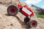 Rc crawler overcoming mountain rise, close-up. Country land adventure, toy suv riding on rock landscape. Entertainment, hobby, rally concept poster