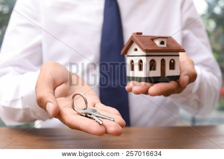 Real Estate Agent Holding House Model And Keys At Table