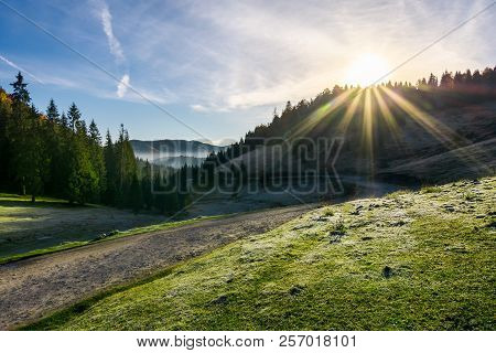 Beautiful Foggy Landscape In Autumn. Winding Road Leads To Distant Valley Full Of Fog. Sun Rise Abov