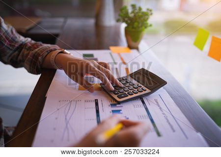 Businesswoman Or Accountant Working On Calculator To Calculate Business Data, And Accountancy Docume