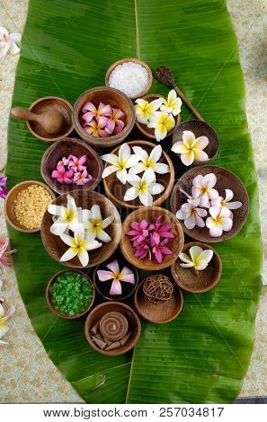 frangipani ,salt ,spoon in wooden bowl and banana leaf texture